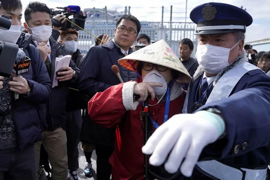A passenger is surrounded as she disembarks the Diamond Princess cruise ship in Yokohama, Japan. Photo - EPA
