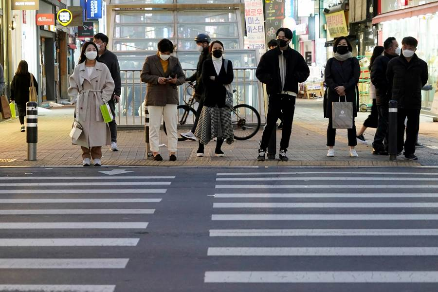 People wait at a crosswalk along the Dongseong-ro shopping street in Daegu, South Korea. The country reported 142 new coronavirus cases on Saturday. © Reuters