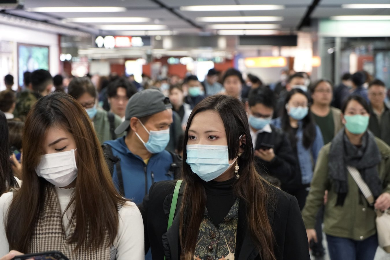 Hong Kong subway passengers wear surgical masks during the coronavirus outbreak. Though it's a global health emergency, it's not yet a pandemic.(Associated Press)