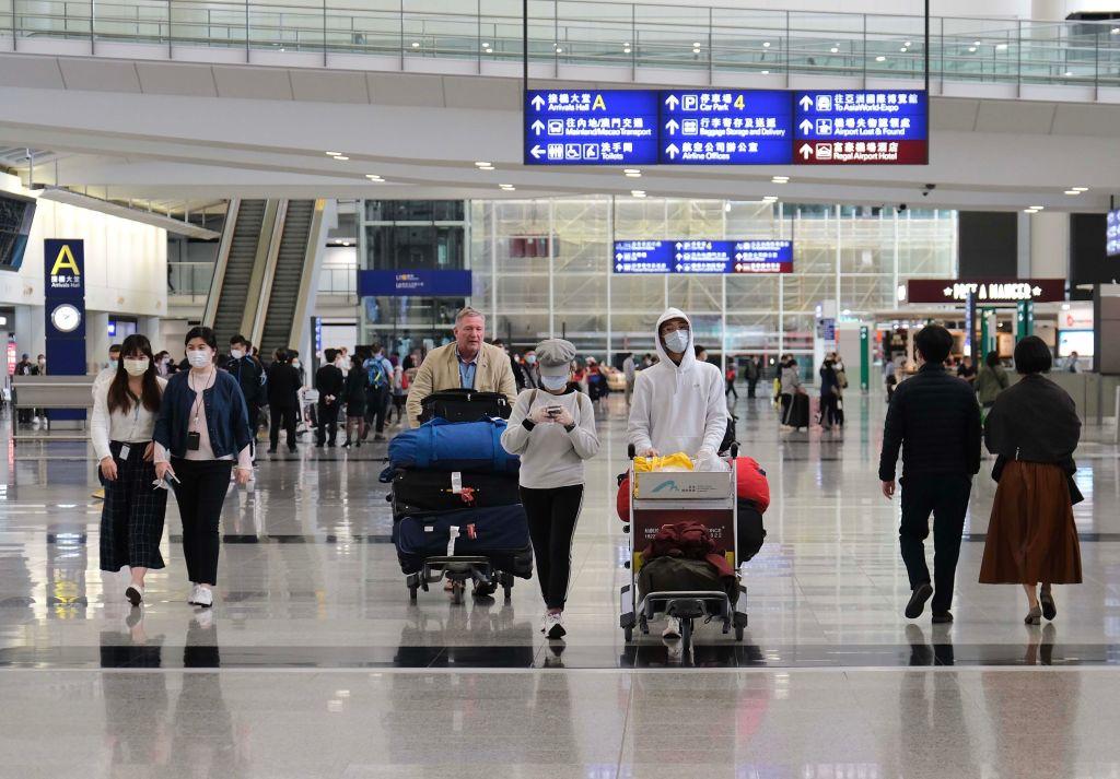 HONG KONG, CHINA - MARCH 17: Passengers wearing masks push their suitcases at Hong Kong International Airport amid the coronavirus, COVID-19 outbreak on March 17, 2020 in Hong Kong, China. (Photo by Qin Louyue/China News Service via Getty Images)
